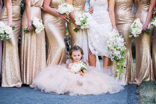 flower-girl-in-tulle-dress-gown-in-front-of-bridesmaids-during-photos-little-bouquet-white-flowers