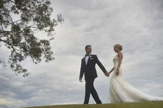 couple-holding-hands-in-wedding-attire-on-grass