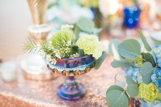 colorful-iridescent-goblet-with-greenery-on-rose-gold-sequin-table-linen