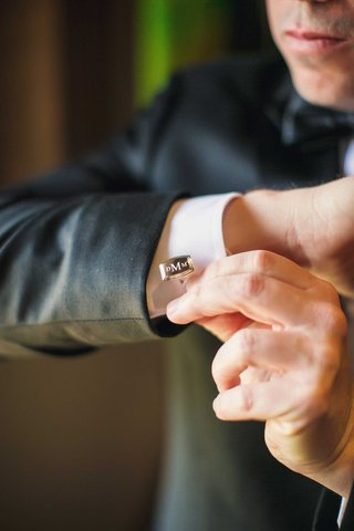 groom-getting-ready-for-wedding-day-putting-on-monogram-three-initial-cufflink