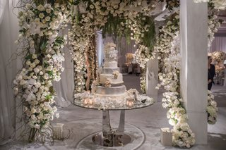 wedding-cake-on-table-multi-layer-feather-silver-white-flowers-greenery-arch-modern-cake-table