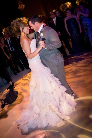 bride-in-strapless-mark-zunino-blush-wedding-dress-with-ruffle-skirt-first-dance-with-smiling-groom