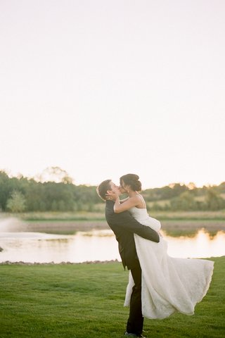 groom-in-black-suit-lifts-and-kisses-bride-in-a-lace-dress-on-a-green-lawn-by-the-water