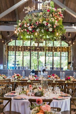 wedding-reception-wood-ceiling-high-beams-chandelier-flowers-peach-pink-twinkle-lights