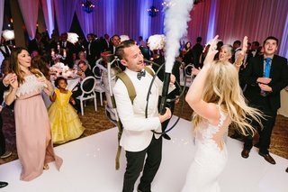 groom-with-carbon-dioxide-tank-at-wedding-reception-to-fill-dance-floor-with-fog