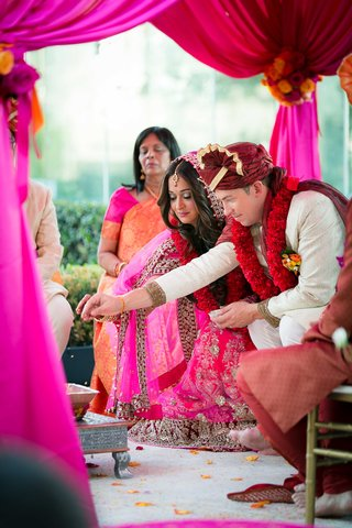 bride-in-lehenga-and-groom-in-sherwani-at-outdoor-indian-wedding-ceremony-with-pink-and-red-canopy