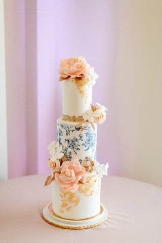 narrow-three-tier-cake-with-blue-floral-tier-and-peach-sugar-flowers