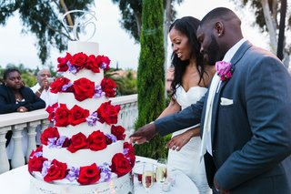 newlyweds-cut-white-cake-with-red-and-purple-flowers