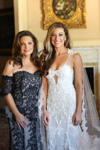 bride-in-monique-lhuillier-wedding-dress-with-cape-veil-and-mother-in-black-lace-dress-long-hair