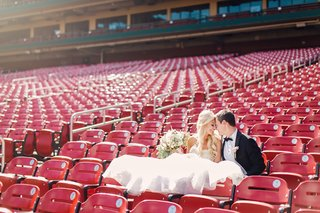 bride-and-groom-in-stadium-chairs-at-busch-stadium-in-st-louis-in-wedding-dress-and-tuxedo