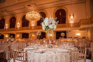 wedding-reception-with-golden-chairs-embroidered-overlays-on-tables-tall-stand-with-white-hydrange