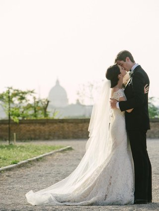 bride-in-lace-wedding-dress-kiss-groom-in-rome-italy