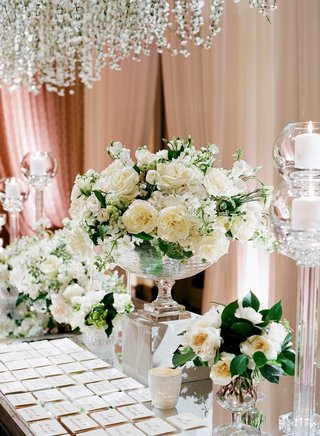 escort-cards-on-mirror-table-with-clear-vases-filled-with-garden-roses-and-other-white-flowers