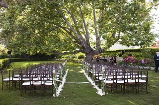 petal-lined-aisle-with-brown-wooden-chairs