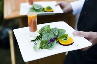 caterer-holding-two-plates-of-salad-appetizer