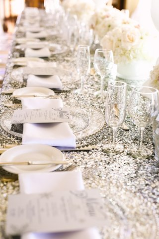 silver-sequin-tablecloths-and-clear-chargers-on-reception-table