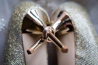 brides-diamond-wedding-ring-and-grooms-band-on-heel-of-jimmy-choo-gold-shoes-metallic