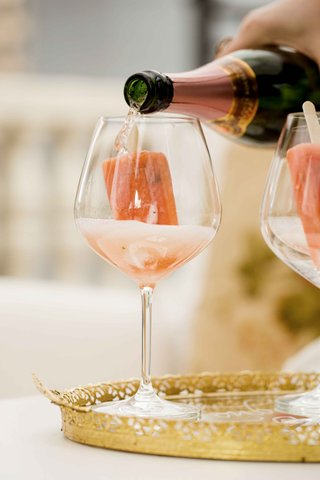 pink-champagne-poured-over-gourmet-popsicles-on-gold-tray