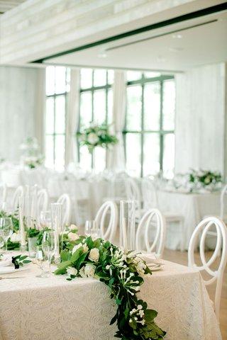 wedding-reception-long-table-white-linen-greenery-white-rose-flower-centerpiece-runner-taper-candles