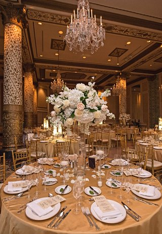 gold-table-linens-white-china-charger-plates-tall-glass-vases-ivory-and-blush-floral-arrangements