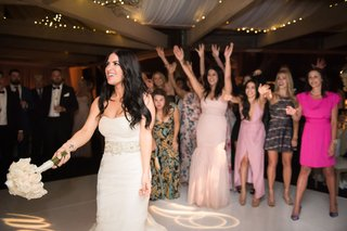 bride-in-vera-wang-does-bouquet-toss-at-wedding-reception