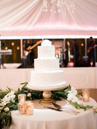 white-wedding-cake-with-gold-pearl-dots-and-fllower-cake-topper-on-gold-stand-cake-table