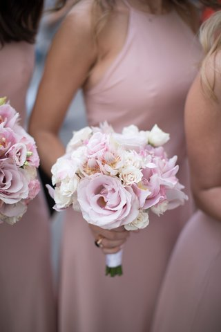 bridesmaids-in-pink-dresses-holding-small-bouquet-of-pink-rose-pink-orchid-white-rose-thistle