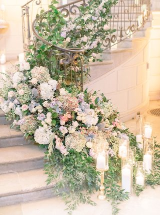 wedding-reception-at-oheka-castle-grand-staircase-decorated-with-greenery-candles-dusty-miller-pink