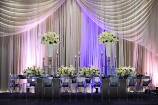 mirror-table-with-clear-chairs-in-front-of-drapery