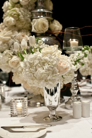 white-reception-table-with-small-centerpiece-in-silver-vase