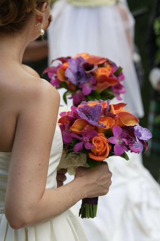 bridesmaid-holds-bouquets-of-colorful-orange-and-purple-flowers