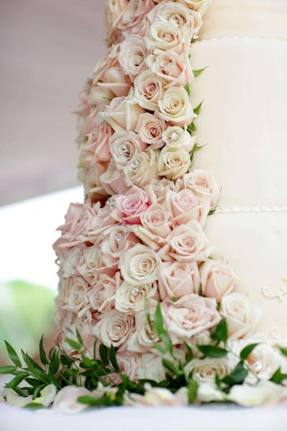 white-wedding-cake-is-decorated-with-cream-and-light-pink-roses-studded-with-crystals