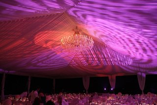 tented-wedding-reception-with-colorful-amber-and-violet-lighting-and-a-maria-theresa-chandelier