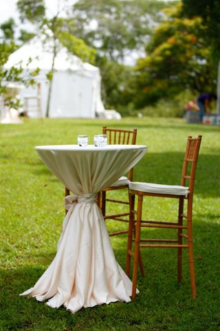 outdoor-wedding-cocktail-hour-with-table-covered-in-white-tablecloth-is-surrounded-by-wood-chairs