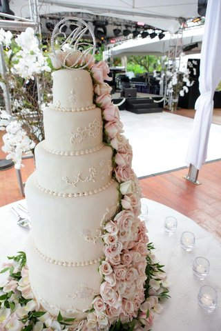 white-wedding-cake-with-light-pink-and-white-roses-topped-with-couples-monogram
