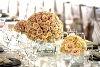 wedding-reception-table-is-decorated-with-golden-pink-roses-in-crystal-vases