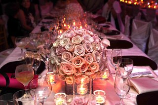 wedding-reception-centerpiece-of-light-roses-surrounded-by-votive-candles