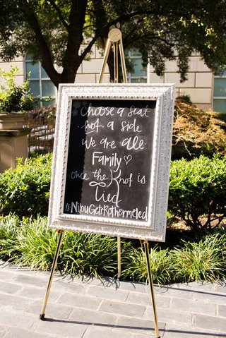 chalk-sign-outside-ceremony-silver-metallic-frame-outdoors-garden-dallas-texas-nilousgotrothermeled