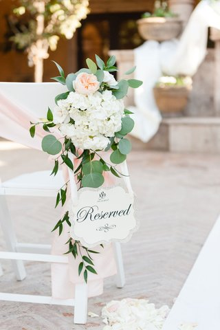 wedding-ceremony-white-chair-pink-ribbon-sash-garden-rose-reserved-sign-die-cut-outdoor-ceremony