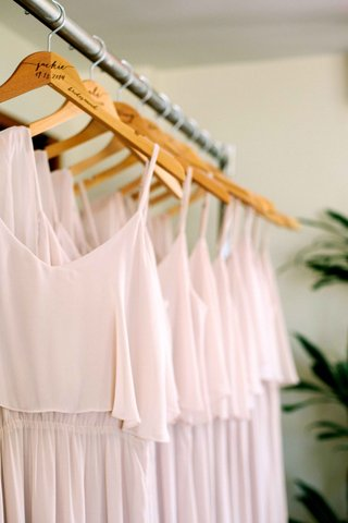light-pink-one-shoulder-joanna-august-bridesmaid-gowns-on-hangers