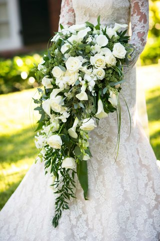 bride-in-isabelle-armstrong-wedding-dress-holding-cascading-bouquet-of-green-leaves-white-flowers