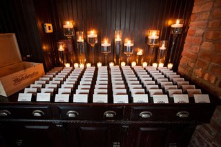 new-york-wedding-reception-escort-card-tents-on-table-desk-with-candles-in-back-and-wood-box