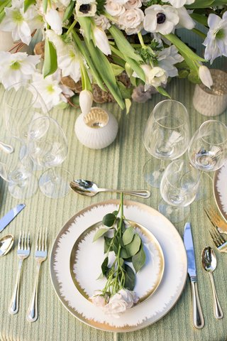 white-and-gold-charger-plates-on-green-table-linen-pink-stem-flowers-silverware-floral-arrangement