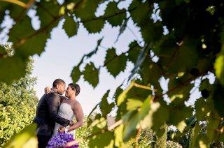 bride-in-strapless-wedding-dress-hugging-groom-portrait-through-leaves-artistic-wedding-photo-purple