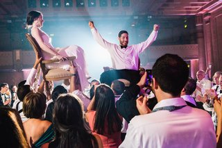 newlyweds-lifted-up-during-the-horah-at-jewish-wedding-reception-in-atlanta