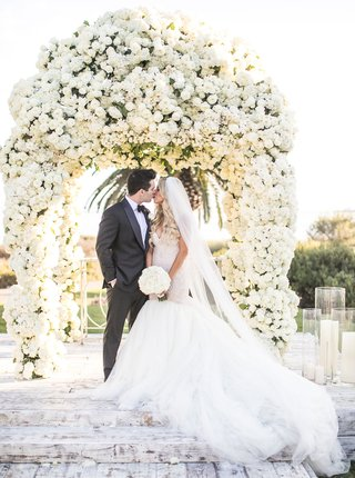 bride-in-galia-lahav-mermaid-wedding-dress-kissing-groom-in-front-of-canopy-of-white-flowers