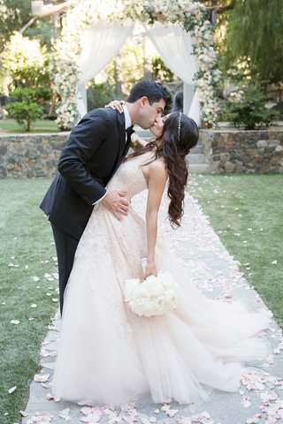 bride-in-blush-monique-lhuillier-wedding-dress-and-jeweled-headband-groom-in-suit-dipped-for-kiss