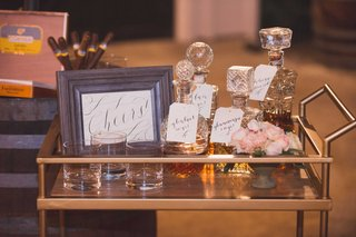 gold-bar-cart-with-cheers-calligraphy-print-crystal-decanters-filled-with-alcohol-liquor-glasses