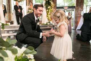 groom-at-wedding-gives-flower-girl-a-lollipop-for-making-it-down-the-aisle