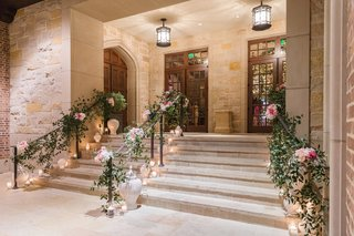 stairway-into-wedding-reception-with-candles-greenery-garland-on
